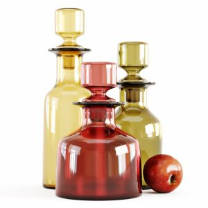 Three Decorative Glass Bottles And Red Apple